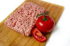 Carne tritata su una scheda di taglio con il pomodoro Fotografia Stock