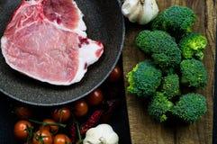 Carne in una pentola da cucinare, completato con i pomodori, i broccoli e l'aglio Immagine Stock Libera da Diritti