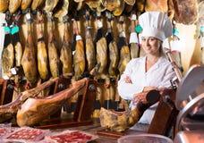 Carne vendedora femenina alegre del prosciutto Fotografía de archivo