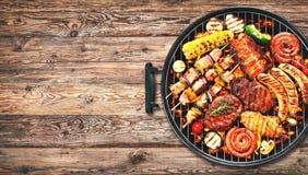 Carne y Bratwurst asados a la parrilla deliciosos clasificados con las verduras encendido foto de archivo