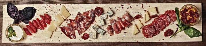 Carne y queso en un tablero de madera adornado con las salsas de la albahaca Foto de archivo