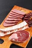 Carne y salchicha de los ciervos en tabla de cortar Imagen de archivo