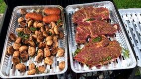 Carne y setas asadas a la parrilla de cerdo en la parrilla Barbacoa Preparación de comida en las bandejas de aluminio mientras qu almacen de metraje de vídeo