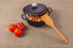Carne y verduras en la cacerola, y tomates al lado de la tabla Imágenes de archivo libres de regalías