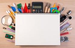 Carnet au-dessus des fournitures scolaires ou des fournitures de bureau sur la table d'école photo stock