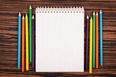 Carnet avec des crayons de couleur Images stock