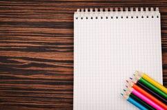 Carnet avec des crayons de couleur Photographie stock libre de droits
