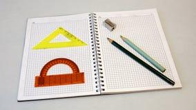 Carnet avec des crayons et des règles sur un fond clair Images libres de droits