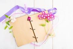 Carnet avec des fleurs pour la femme ou la fille au-dessus de la table en bois blanche Photos libres de droits