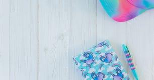 Carnet avec la licorne et l'arc-en-ciel de lama avec le stylo coloré de gel et chapeau d'arc-en-ciel sur le fond en bois blanc Id images libres de droits
