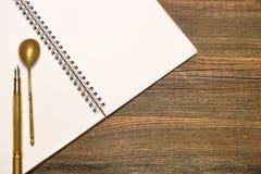 Carnet avec la page vide, la cuillère et le Pen On Wood Table Image libre de droits