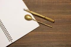 Carnet avec la page vide, la cuillère et le Pen On Wood Table Images libres de droits