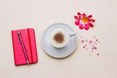 Carnet avec la tasse du café et de la fleur sur en bois Photographie stock