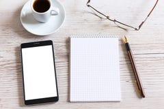 Carnet avec la tasse intelligente de téléphone et de café sur la table en bois Photos stock
