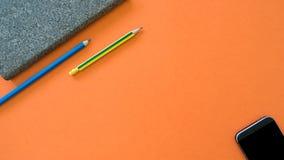 Carnet avec le crayon et le smartphone sur le fond orange Business Photographie stock libre de droits