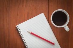 Carnet avec le crayon et une tasse de café sur la table en bois Photos libres de droits