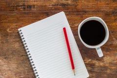 Carnet avec le crayon et une tasse de café sur la table en bois Image libre de droits