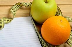 Carnet avec le fruit de pomme et d'orange Photographie stock libre de droits