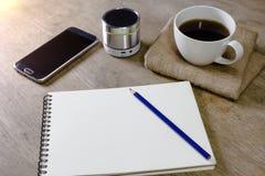 Carnet avec le haut-parleur et le smartphone de crayon de café sur le bureau Photographie stock libre de droits