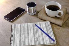 Carnet avec le haut-parleur et le smartphone de crayon de café sur le bureau Images stock