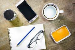 Carnet avec le haut-parleur et le smartphone de crayon de café sur le bureau Photo stock
