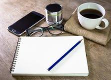 Carnet avec le haut-parleur et le smartphone de crayon de café sur le bureau Image stock