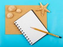 Carnet avec le stylo et les étoiles de mer et les coquillages, d'isolement sur b bleu Images stock
