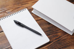 Carnet avec le stylo et livre avec la couverture blanche sur la table en bois photographie stock