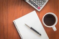 Carnet avec le stylo et une tasse de café sur la table en bois Image libre de droits