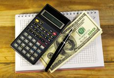Carnet avec le stylo-plume, billets de banque, calculatrice sur un en bois merci Photographie stock libre de droits