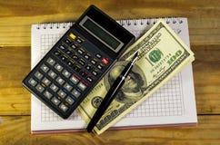 Carnet avec le stylo-plume, billets de banque, calculatrice sur un en bois merci Image stock