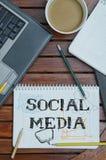 Carnet avec le texte à l'intérieur du media social sur la table avec du café et Image libre de droits