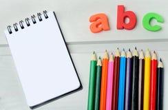 Carnet avec les crayons colorés photographie stock libre de droits