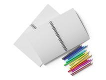 Carnet avec les crayons colorés sur le fond blanc Photos stock