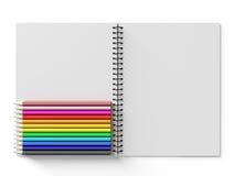 Carnet avec les crayons colorés sur le fond blanc Photo libre de droits