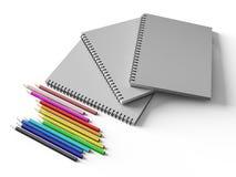 Carnet avec les crayons colorés sur le fond blanc Images stock