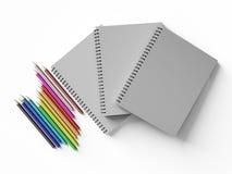 Carnet avec les crayons colorés sur le fond blanc Photographie stock