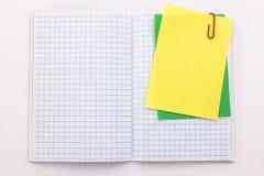 Carnet avec les feuilles de papier jaunes et vertes avec du Cl de papier rouge Photographie stock libre de droits