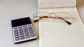 Carnet avec les verres et la calculatrice sur un fond clair Images stock