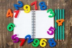 Carnet avec quatre crayons et nombres colorés Photos libres de droits
