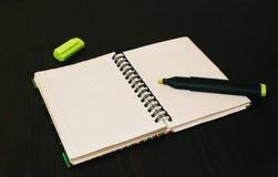 Carnet avec un marqueur sur la table, ouverte sur une page blanche Photographie stock libre de droits