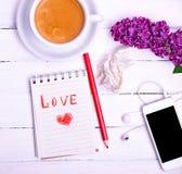 Carnet avec une inscription dans l'amour rouge de crayon Photographie stock libre de droits