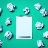 carnet blanc avec le stylo sur un fond vert parmi les boules de papier Le concept de produire des id?es, inventant de nouvelles i images stock