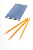 Carnet bleu et crayons jaunes sur un fond blanc Images stock