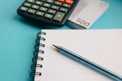carnet clair, stylo, paquet d'euro billets de banque et une calculatrice sur un fond bleu photos stock