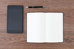 Carnet, comprimé et stylo sur une table en bois Espace de travail pour un jou Photo stock