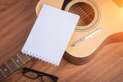Carnet, crayon et lunettes de guitare Photographie stock libre de droits