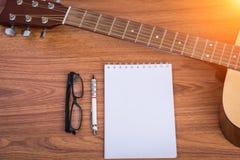 Carnet, crayon et lunettes de guitare Image stock