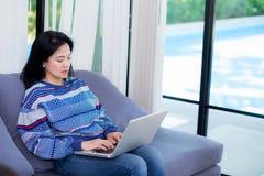 Carnet d'ordinateur de plan rapproché sur le sofa avec la femme asiatique pour le travail dans le mode de vie du concept de femme images libres de droits