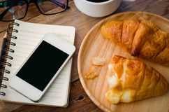 Carnet de café de croissants et téléphone intelligent sur la table en bois - modifiez la tonalité le vintage photo libre de droits